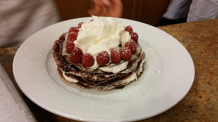 A chocolate crepe cake layered with fluffy, light whipped cream and jam.